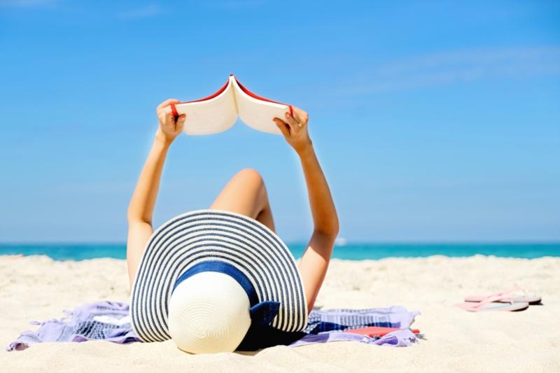 Frau, die am Strand liest